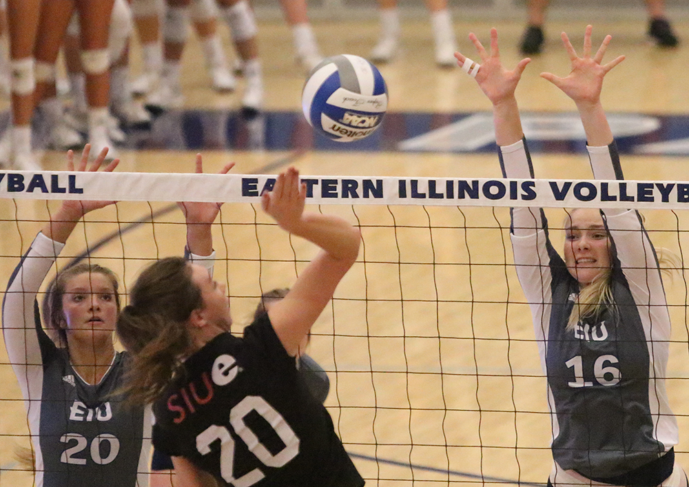 File Photo | The Daily Eastern News Katie Sommer (left) and Maggie Runge (right) try to block a Southern Illinois Edwardsville player's hit during Eastern's 3-0 victory in Lantz Arena in September 2018.