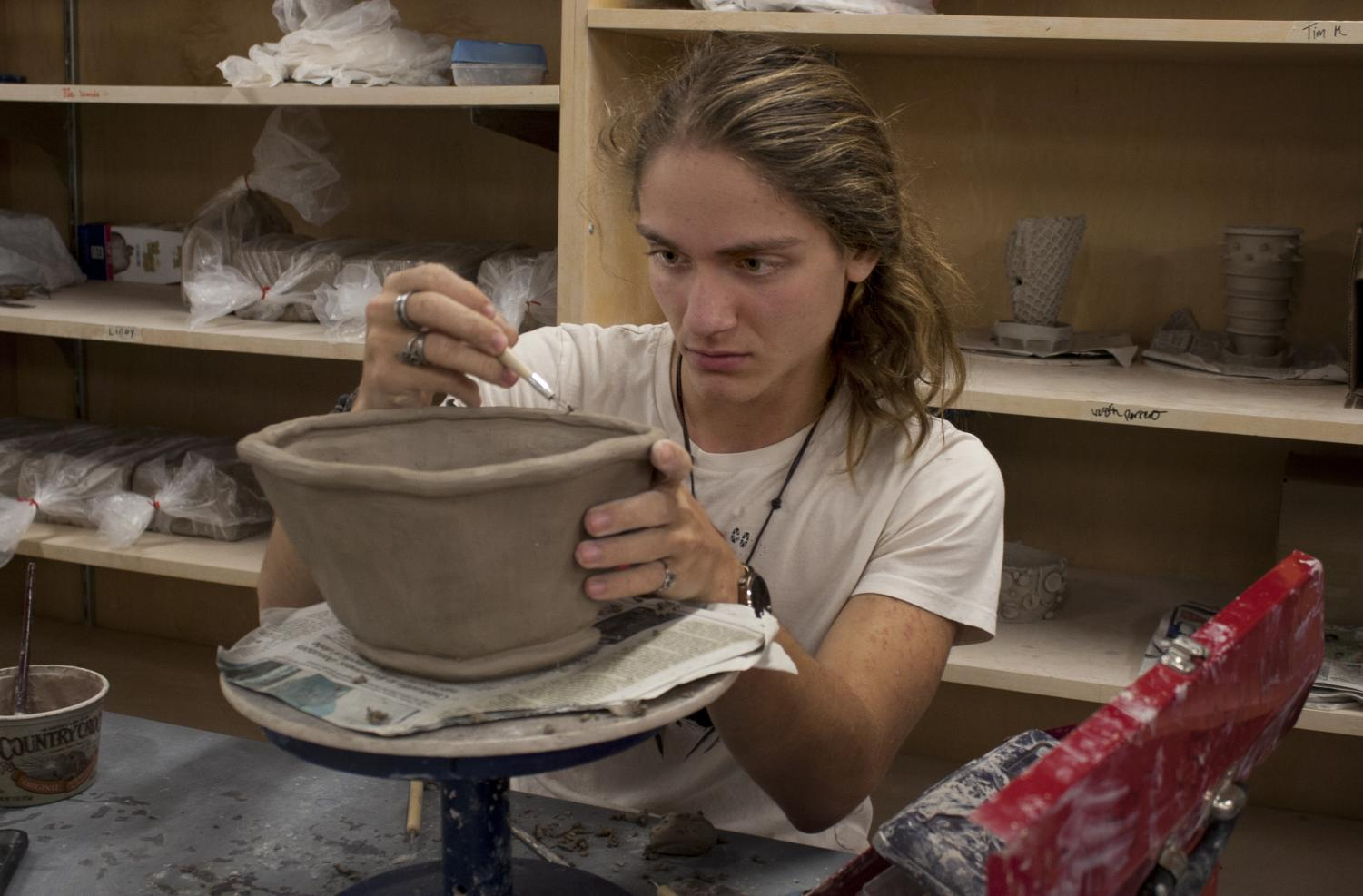 Westin Perrero, a sophomore art education major, works on his pottery project while his other projects dry on the shelves in the Doudna Fine Arts Center Sunday afternoon. Perrero said his favorite part about taking art classes at Eastern is the connection between the teachers and students.