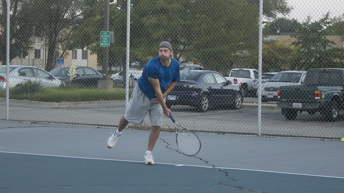 Jeremy Kurzinski, an alum of Eastern, plays tennis against his friend on the tennis courts behind Thomas Hall on Thursday afternoon. Kurzinski said they come out twice a week to play tennis or basketball. He said that he also comes out to support the basketball team when they have home games.
