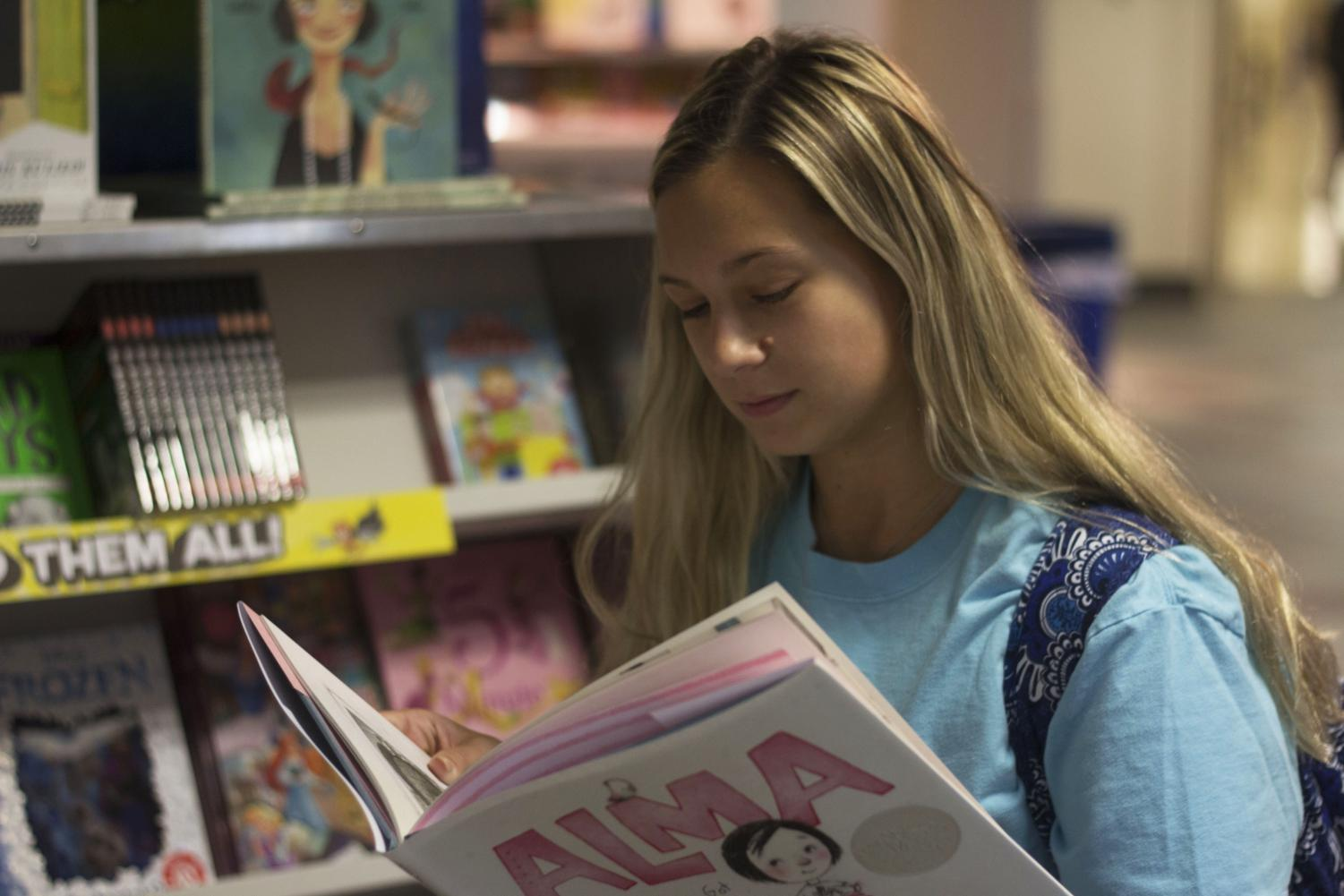 Halie Michalski, senior elementary education major, checks out the books at the Scholastic Book Fair held in Buzzard Hall on Monday. Michalski is the Vice President of Eastern's chapter of the Illinois Reading Council, which hosts the book fair.