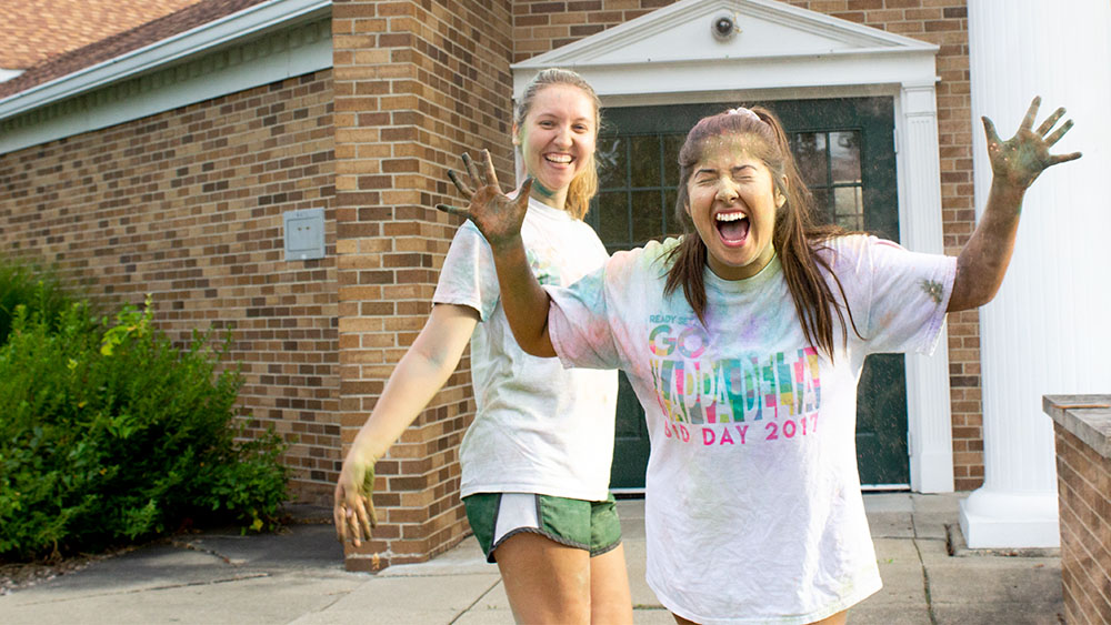 Kendall Kurza, a junior psychology major, surprises Alyssa Bitner, a sophomore communication disorders and sciences major, with chalk powder during a Kappa Delta Sorority sisterhood event on Tuesday.