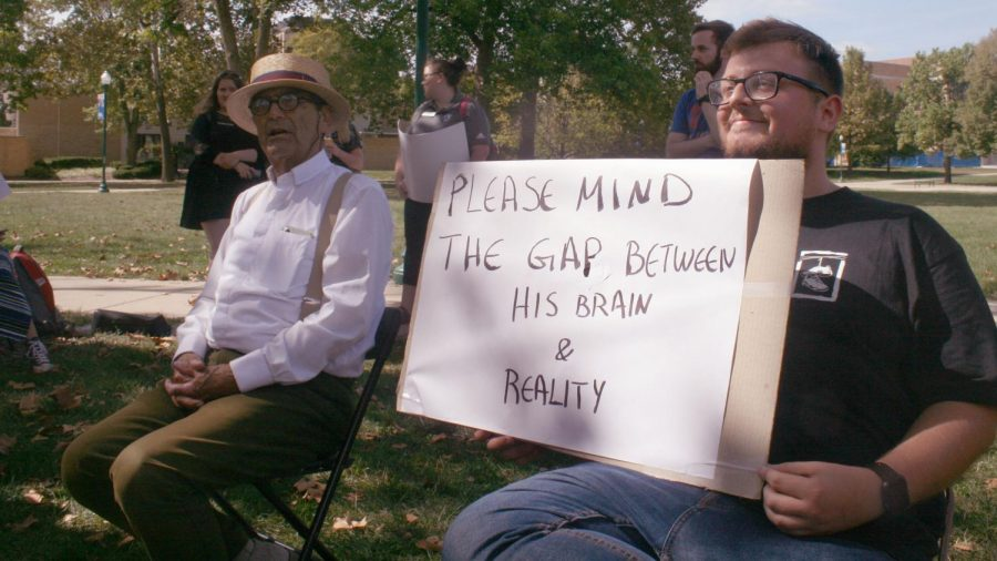Graduate student Nik Pouliarekos  (right), holds a sign next to Jed Smock, a member of Campus Ministry USA, during Smock's question-and-answer style talk Tuesday afternoon in the Library Quad.