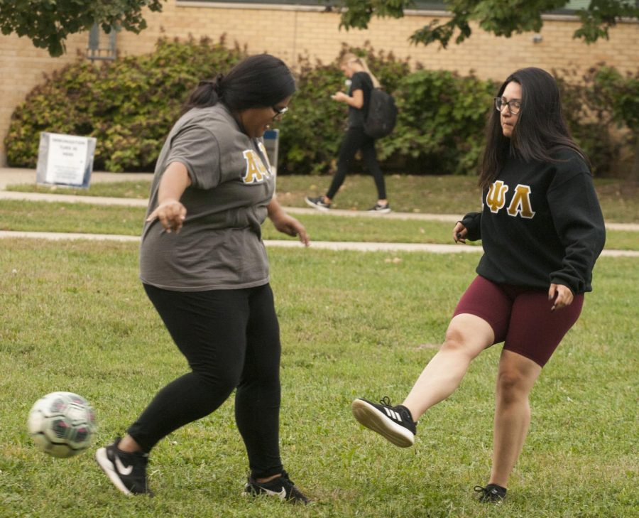 """Jennifer Escobedo, a junior majoring in nursing, and Isela Diaz, a senior English major: creative and professional writing, play soccer during the """"Soccer On the Quad"""" event for Latino Heritage Month."""