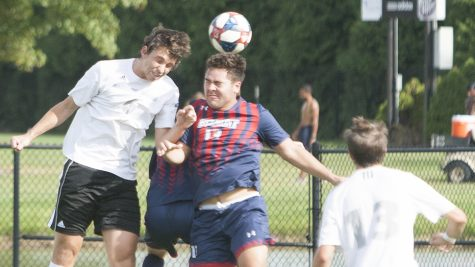 Dillan Schorfheide | The Daily Eastern News  Davi Girardi heads a cross toward Belmont's goal as a defender jumps with him. Girardi scored the game-winning goal in overtime to give Eastern a 3-2 win over Belmont Tuesday at Lakeside Field.