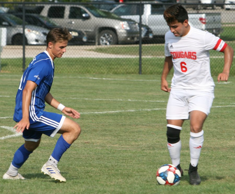Karina Delgado | The Daily Eastern News Christian Sosnowski defends an opponent who is dribbling the ball in the middle of the field. Eastern defeated St. Xavier 2-0 Tuesday at Lakeside Field in the Panthers' home opener.