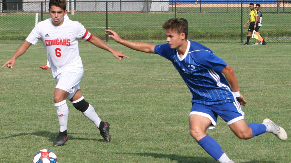 Karina Delgado | The Daily Eastern News Christian Sosnowski runs to gain possession of the ball as a defender starts to guard him. Eastern defeated St. Xavier Tuesday in its home opener 2-0 at Lakeside Field.