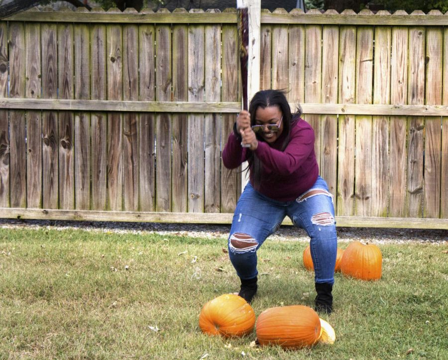 """Courtney Cager, a junior accounting and fashion merchandising major, smashes pumpkins with Alpha Sigma Alpha, Alpha Sigma Tau and Kappa Delta to help with Phi Kappa Theta's philanthropy project on Thursday evening at Ninth Street. """"I love helping out other Greek's philanthropy on campus while spending time with my sisters,"""" she said."""