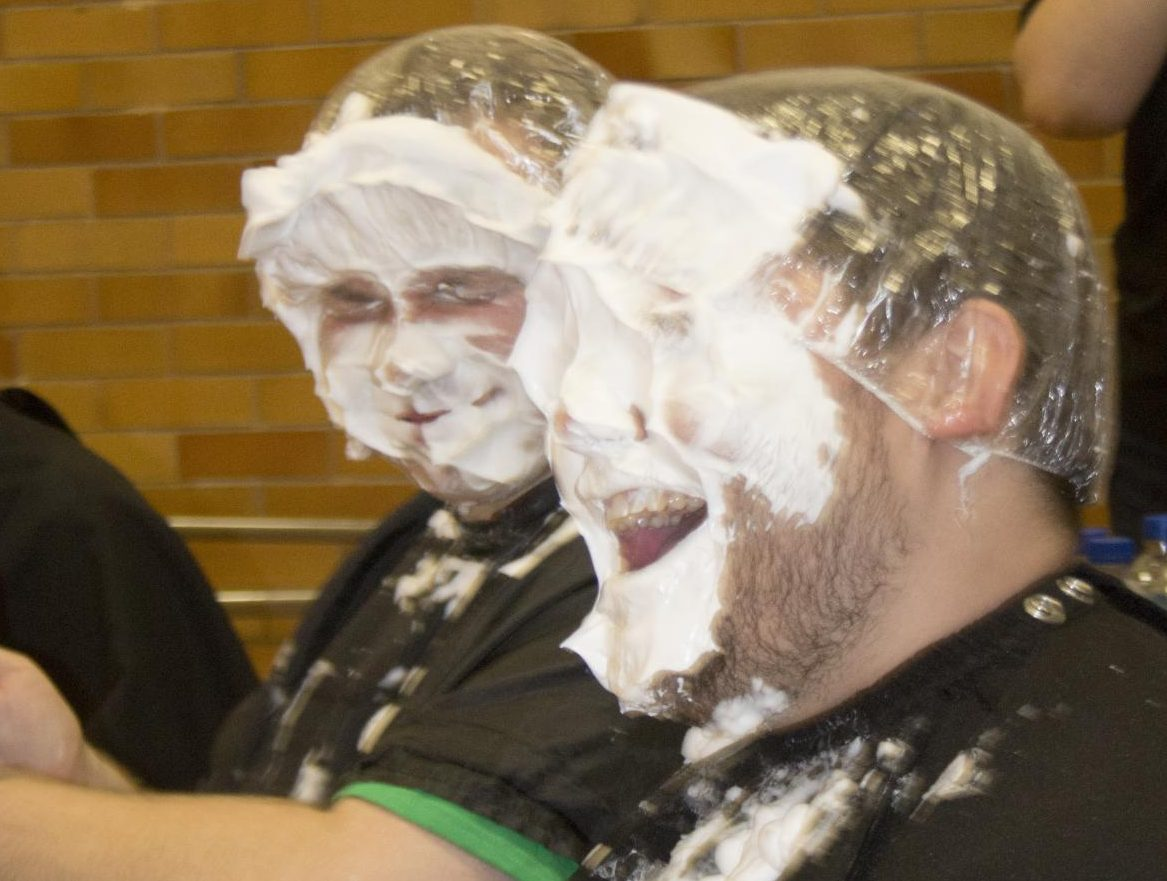 Joshua Grostlin (front), a college student affairs graduate student, and Kurt Ness (behind), a college student affairs graduate student, get pied in a face during the Rush Hour event for homecoming week.