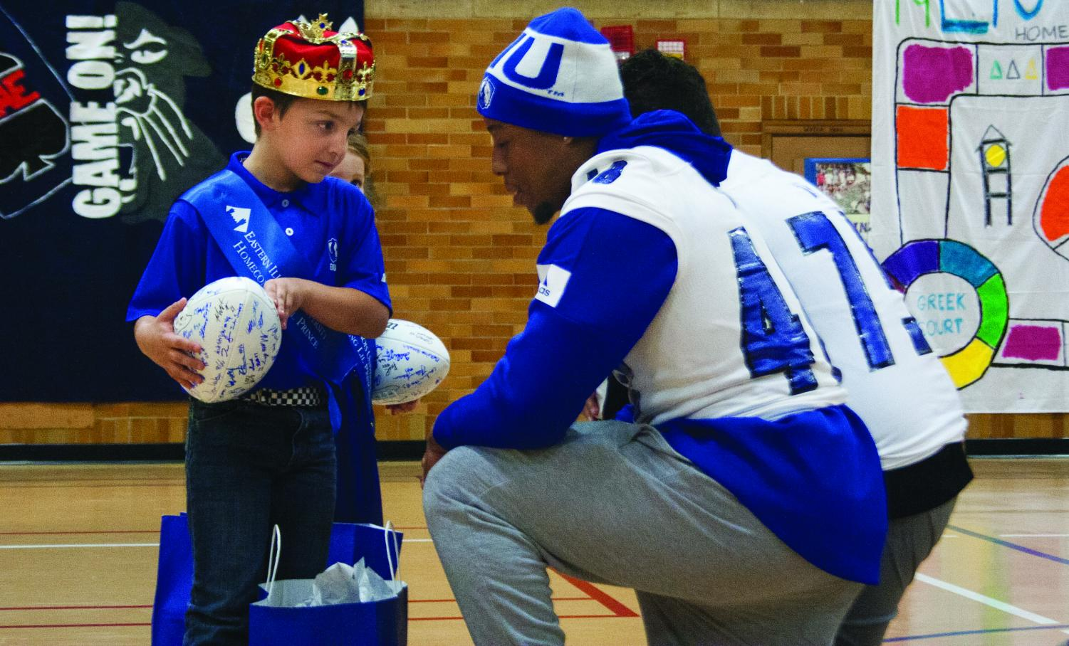 Alex Smith, a junior accounting major, and football player, hands a goodie bag to Eastern's Little Prince, Mason Koehler, during coronation and pep rally in McAfee Gym on Thursday night. During the pep rally, sororities, fraternities, cheerleaders, and the pink panthers competed in games to win prizes.
