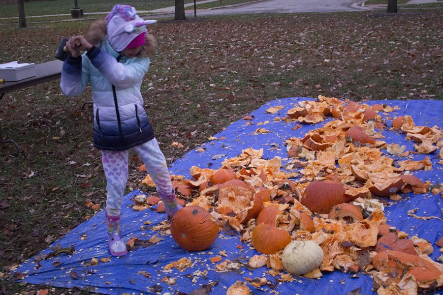 A trick-or-treater smashes a pumpkin during the Greeks and Treats event at Greek Court on Thursday. People were able to purchase pumpkins for only $5 at the event. The proceeds went to HOPE, the Sarah Bush Lincoln Cancer Center and the Charleston Food Pantry.