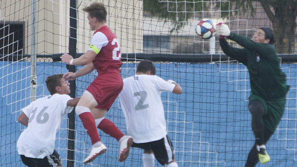 Dillan Schorfheide | The Daily Eastern News Jonathan Burke punches a crossed ball away as an attacker misses his header attempt. Eastern defeated IUPUI 1-0 Oct. 1 at Lakeside Field.