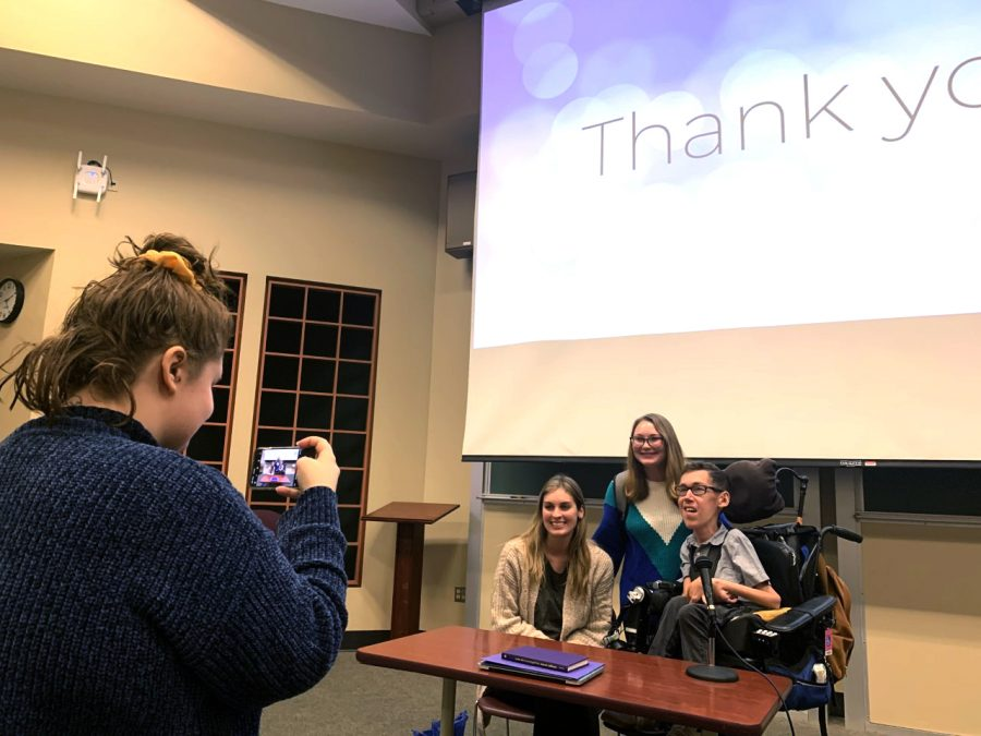 Cameron Kraig, a junior special education major, takes a photo of her friend Sydney Cacioppo with YouTube stars Hannah Aylward and Shane Burcaw at Buzzard Auditorium on Monday night. Kraig and Caioppo expressed their excitement over Aylward and Burcaw coming to Eastern and hearing the two talk about their love and fighting against the stigma against disabilities.