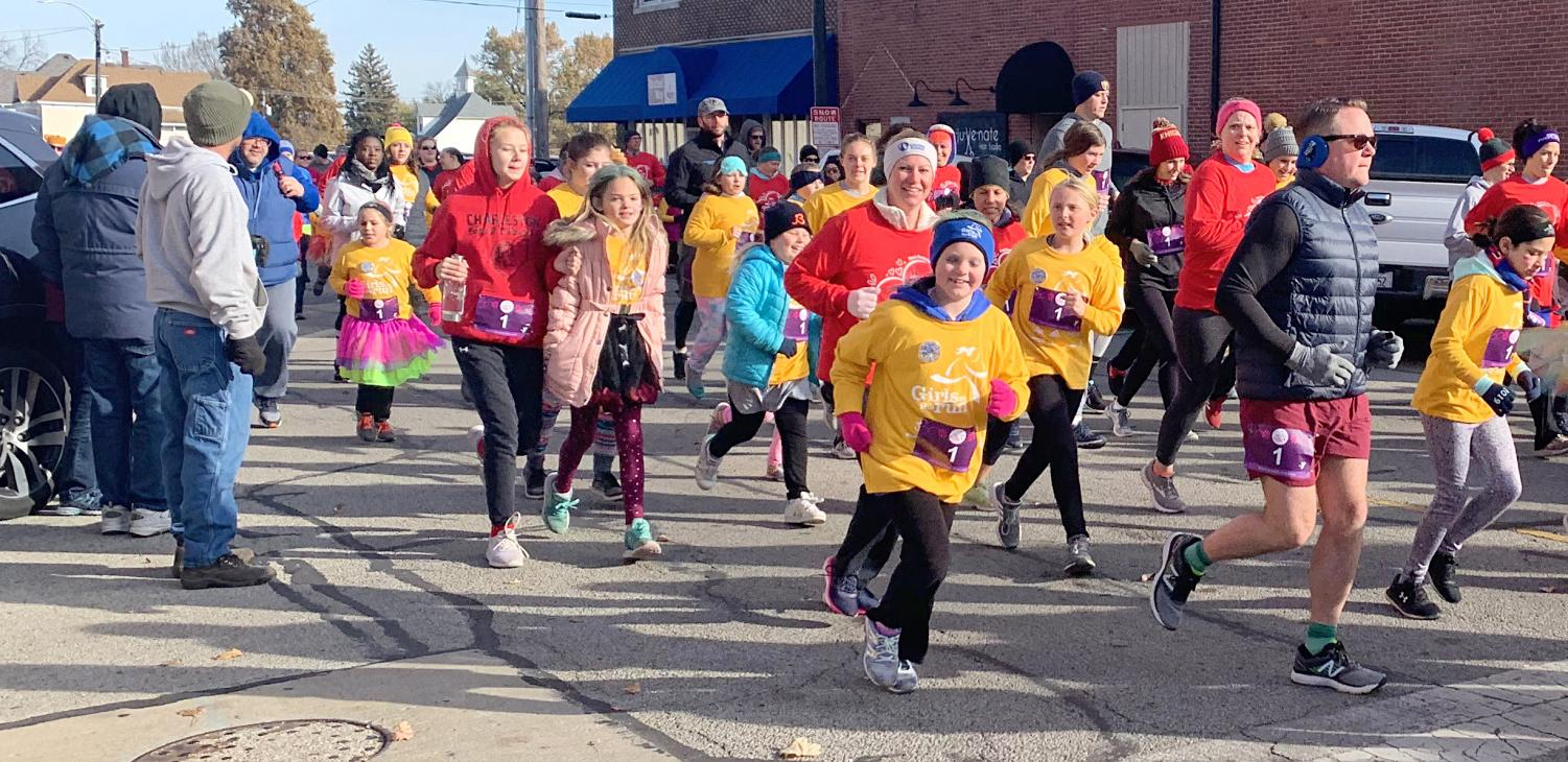 Community members run on the corner of Broadway Street and 16th Street in Mattoon, where The Girls on the Run 5K running route began, Saturday morning. The run had approximately 400 race participants.