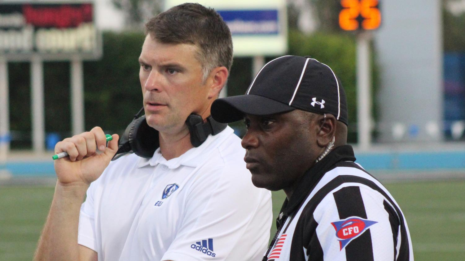 Eastern head coach Adam Cushing talks with the line judge during an official review in the Panthers' game against Tennessee Tech Sept. 28. Eastern lost the game 40-29.