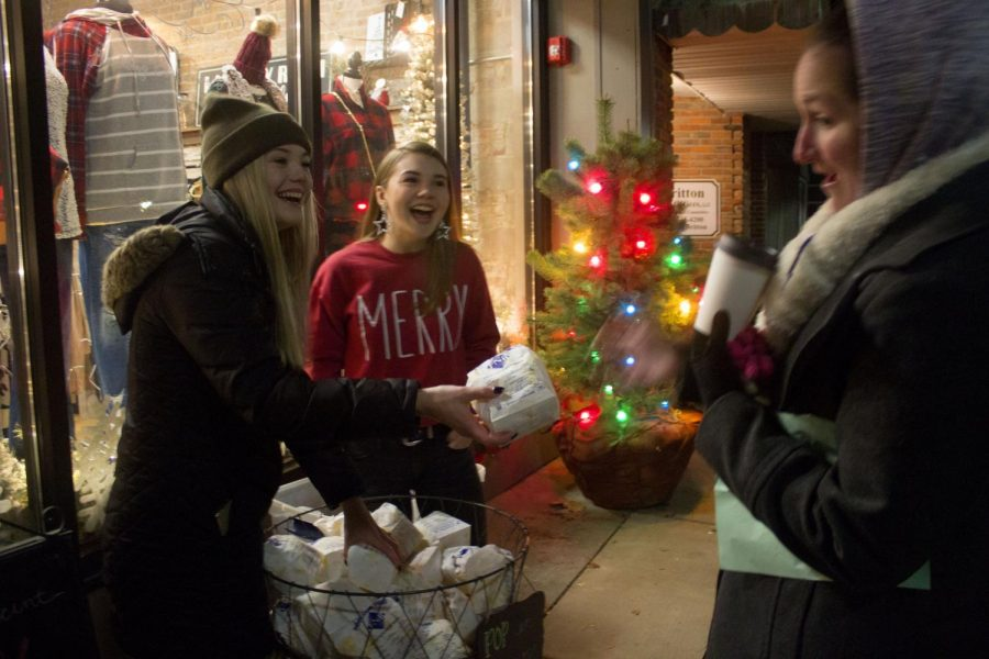Dakota Crowder, an early childhood education senior, and Annie Crowder, a fashion merchandising and design freshman, pass out free popcorn in front Plush Boutique at downtown Charleston square during the Christmas in the Heart of Charleston Saturday night.