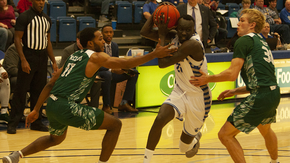 Adam Tumino | The Daily Eastern News Eastern guard Deang Deang drives between two Green Bay defenders Dec. 7 in Lantz Arena. Deang had 12 points, five assists and four rebounds in the game, a 93-80 win for Eastern.