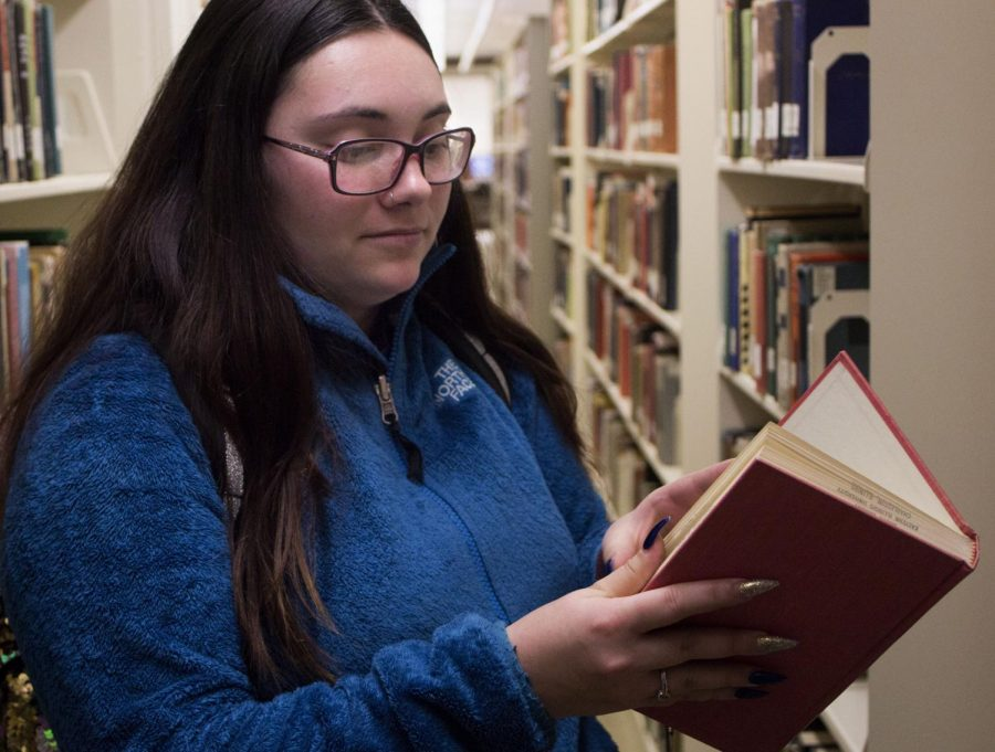 Gianna Angiulo, a senior art major, looks through the book stacks for an interesting read in Booth Library on Monday afternoon. Angiulo said she enjoyed reading but stopped because she did not have enough time.