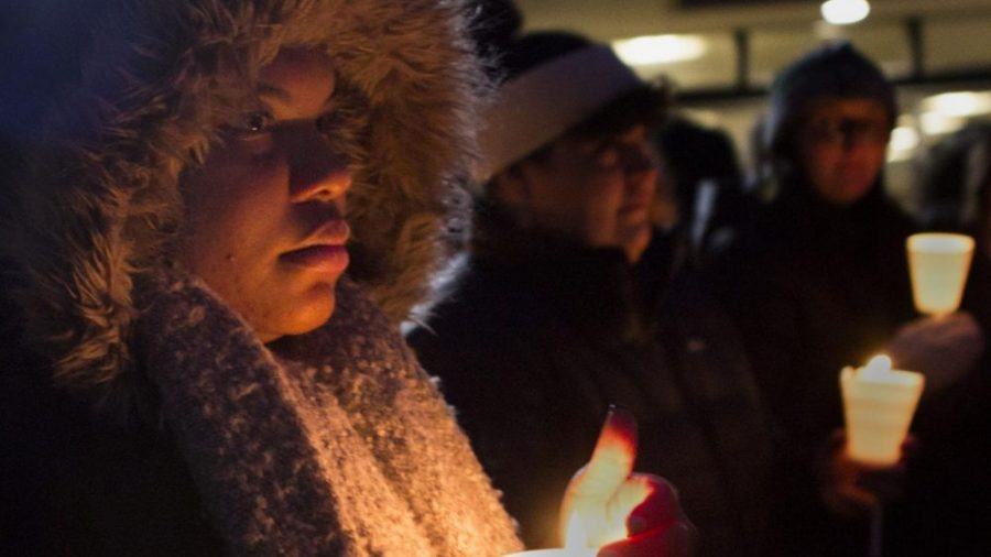 Raven Ramsey, a construction management major, protects her candle's flame against the wind during the candlelight vigil and celebration for Martin Luther King Jr. lead by the Alpha Phi Alpha fraternity on Monday night. Ramsey said she wanted to honor Martin Luther King Jr.'s actions and his