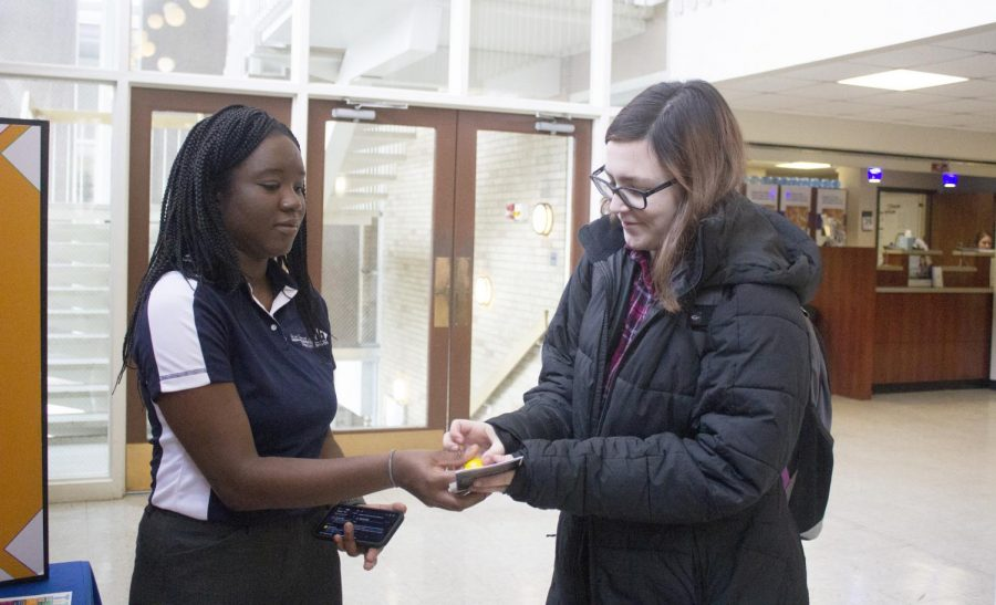 """During the Diversity Action Council tabling event, Samari Abdoulaye-Pedila, senior psychology major, gives a student a stress ball and pamphlet on Wednesday afternoon. The event was called """"The Words We Use,"""" and its purpose was to create dialogues about the importance of word choice and how it can affect others."""