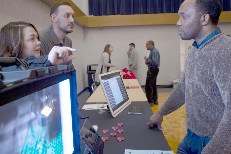Igho Doghudje (right), a graduate student majoring in technology, speaks with HR specialists Sarah Steinbaugh and Alec Hart from the company Watchfire, during Wednesday's job fair at the Grand Ballroom of the Martin Luther King Jr. University Union. Doghudje said showing potential employers interest and getting to know them before submitting resumes is beneficial to the hiring process.