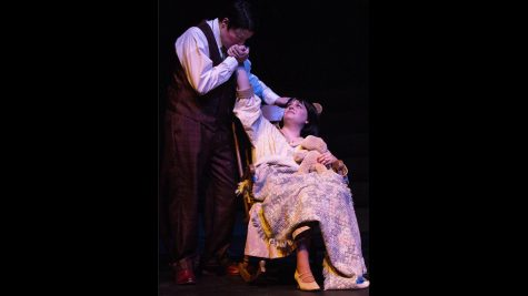 "Josh Hernandez, a junior majoring in finance and plays Tom (Catherine's husband), and Merri Bork, a junior majoring in theatre and plays Catherine, perform during a dress rehearsal for ""These Shining Lives"" in The Theatre. In this scene, Tom is comforting Catherine after she woke up from a nightmare about dying and tells her that she is still here with him."