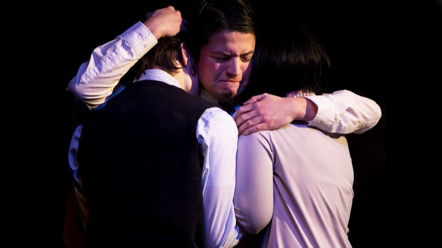 """Tom, played by junior theatre major Josh Hernandez, comforts his children, played by freshman triple majoring in theatre, psychology, and criminology and freshman theater arts major Aidan Collins, after Catherine, played by junior theatre major Merri Bork, had yelled at them to go to bed during a dress rehearsal for """"These Shining Lives"""" in The Theatre. In this scene, Tom, Catherine and their children were coming to terms with Catherines diagnosis of extreme radium poisoning."""