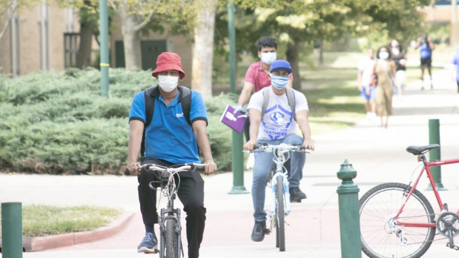 Kanaka Kaviraj (front), Pubudu Perea (middle) and Praha Naga (back), all second-year chemistry graduate students, ride their bikes to South Quad Wednesday afternoon. All three were heading to COVID-19 testing site before their classes.