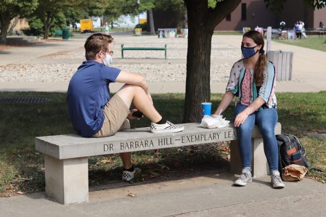 Conner Sanders (left), a sophomore music therapy major, and Emily Thorpe, a freshman music major, sit and eat on a bench near the Library Quad Thursday afternoon.