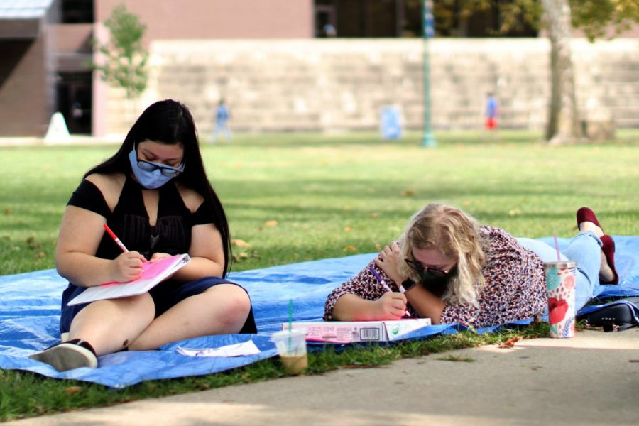 Victoria Tegge (left), a nutrition and dietetics major, and Olivia Triplett, an elementary education major, color together in the North Quad on Monday afternoon.