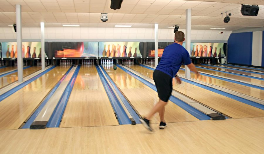 Nick Wilson, a sports administration grad student and manager at the bowling alley, bowls at the EIU Lanes in the Martin Luther King Jr. University Union Wednesday. Wilson said the lanes have been busy recently despite COVID-19 precautions.