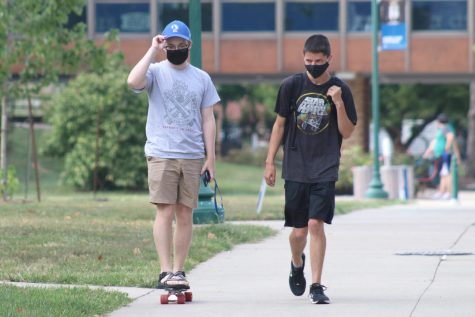Conner Sanders (left), a sophomore music therapy major, long boards as Nick Myer (right), a sophomore chemistry major, walks with him after doing homework in the Dounda Hall red room Monday evening. Sanders and Myer said they were on their way to get food from Thomas Hall.
