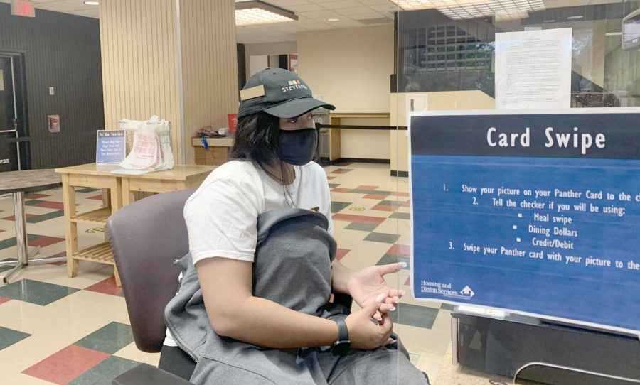"""Angelia Cosey, a sophomore nursing student, swipes students in at Stevenson dinning hall on Sunday evening. Cosey said she enjoys working at Stevenson and that """"everyone is warm and helpful here."""""""