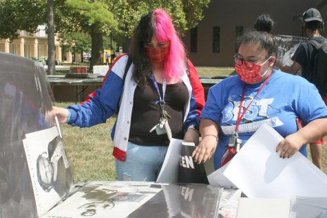 Kathya Morales (left) a freshman history education major, and Jacky Rivera (right) a freshman elementary education major look through posters at the Library Quad Tuesday afternoon. Morales and Rivera said they were walking around campus and decided to check out the poster sale after seeing the set up.
