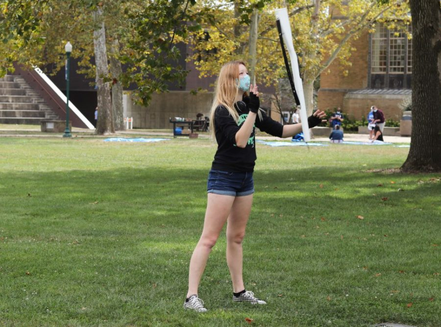"""Ally Turner, a junior environmental biology major, practices for the Panther Marching Band in the Library Quad Tuesday afternoon. Turner said she is """"writing guard solo for EIU Panther Marching."""""""