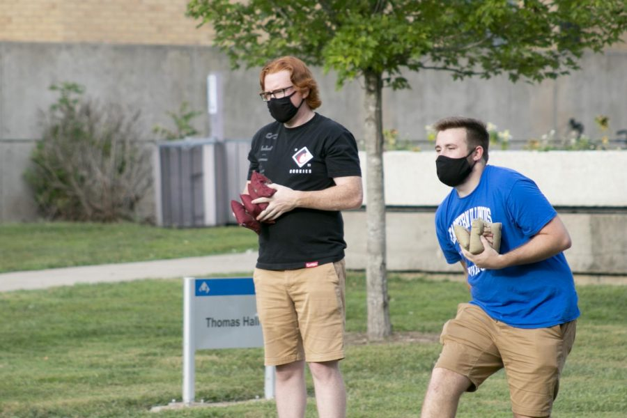 """Joseph Toner (left), junior public relations in health  major and Andrew Raymond (right), freshman computer and information technology major partipate a game of bags during 'Meet the Fraternities' Wednesday evening. Raymond said that rushing for greek life is """"pretty fun so far."""""""