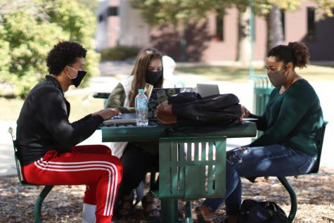 "Josiah Wright (left), a junior mathematics education major, Emily Weber (middle), a sophomore mathematics education major, and Mattie Land, a sophomore family and consumer science major, study in the library quad. The group commented that they were ""studying and trying to stay safe for midterms."""