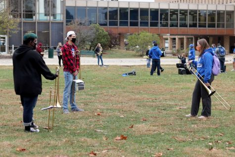 From left to right: Sean Hayes, a sophomore music education major, Lucas Grindley, a freshman broadcast journalism major and Savanna Wooten, a sophomore music education major, prepare for rehearsal on the Library Quad Wednesday afternoon.