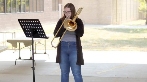 "Savanna Wooten, a sophomore music education major, practices her trombone under an overhang outside Doudna Hall Tuesday afternoon. Wooten said she was ""practicing in the nice weather."""