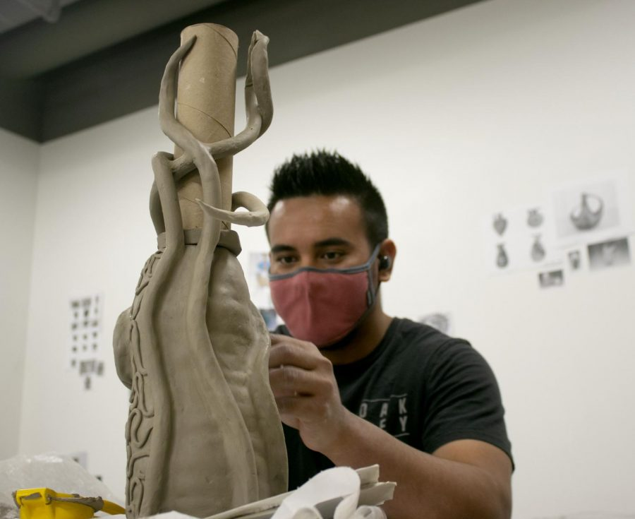 """Kessler Ulberg, a senior studio art major, works on his vase project in Dounda Hall Sunday night. Ulberg explained that he is """"coil building"""" for his Cermaics I project. Ulberg says the """"modern art era"""" pictures in the classroom is what inspired his vase design."""
