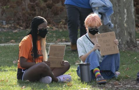 """Aiyanna Ramsey (left), a freshman biology major, and Kenna Bishop (right), a freshman art education major, both sit and hold signs in front of Brother Jed's event in Library Quad Tuesday afternoon. Bishop said they wrote the signs """"a little while go since Brother Jed has come to campus multiple times."""" Ramsey and Bishop said they met at Brother Jed's outings and became friends since then. Ramsey has expressed """"as someone who identifies as both a person of color and a member of the LGBTQ+ community, I recognize how underrepresented we are and it's important that are voices are heard. it's not fair that people believe that can spin religion and spew it back in our faces as hateful speech. You can be both Christian and still indulge in yourself and your identity."""""""