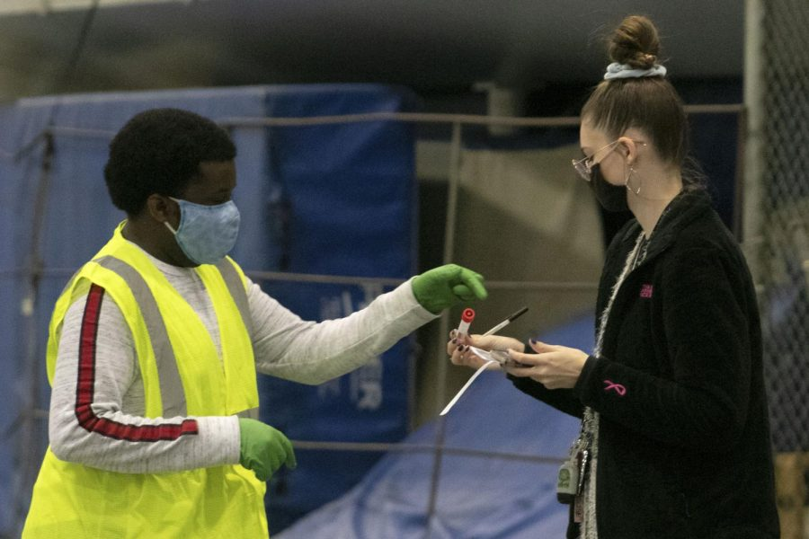 Kate Montgomery (right), a freshman psychology major, gets instruction from Corey Bentley, a senior health administration major, at the COVID-19 testing site in the Lantz Arena Fieldhouse.