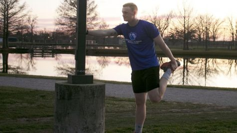Rylan Spangler, a junior kinesiology major, stretches near the campus pond after a run on the Panther Trail Thursday afternoon. Spangler said he usually runs because of ROTC.