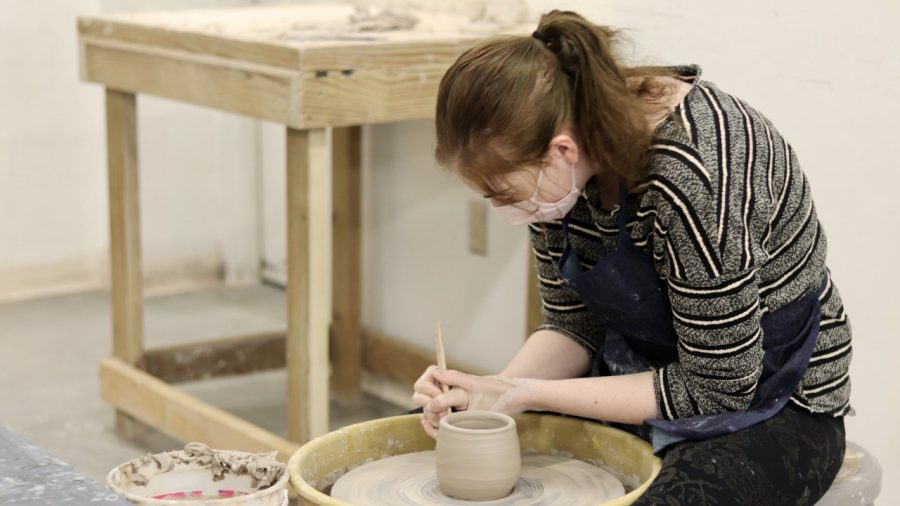 """Megan Miller, a junior art education major, works on her ceramic project for Ceramics II in Doudna Hall over the weekend. """"I'm trying to make a cup but I've never really done it before so I'm just experimenting,"""" Miller said."""