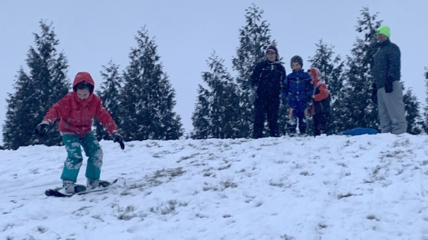 Zoey Lowe (left) snowboards down a hill near Lakeside Field Wednesday afternoon. The Lowe family spent their afternoon sledding and snowboarding down the hill after the area had its first major snowfall of the year.