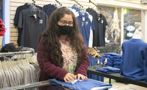 "Desiree Theobald, a senior public relations major, folds t-shirts at Positively 4th Street Records Monday night. Theobald said she has been working at 4th Street for two years. ""I really do enjoy it,"" Theobald said. She also said she enjoys the holidays, homecoming events and state track season in the shop."