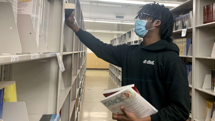 """Chateau Fouchea, a junior criminal justice major, picks up his textbooks Sunday afternoon from Easterns Textbook Rental Service. Fouchea said he is """"excited"""" for the new semester."""