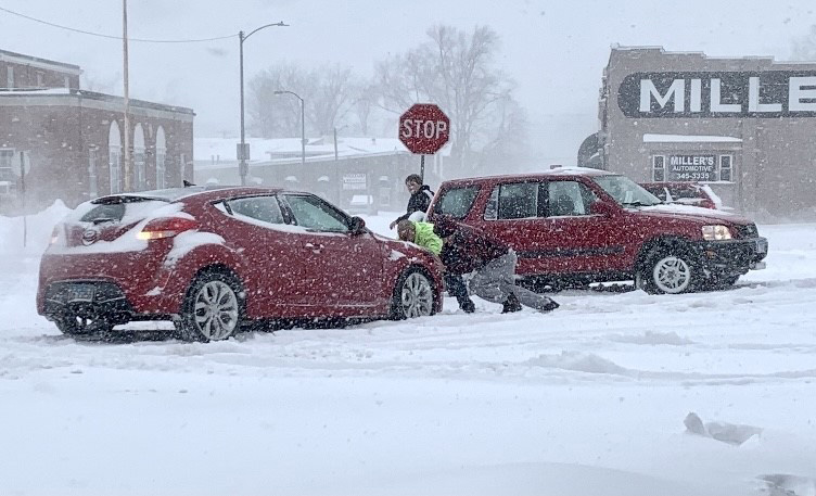 Drivers work to help free a car that got stuck in the snow at the intersection of Madison Avenue and 6th Street in Charleston Monday afternoon.