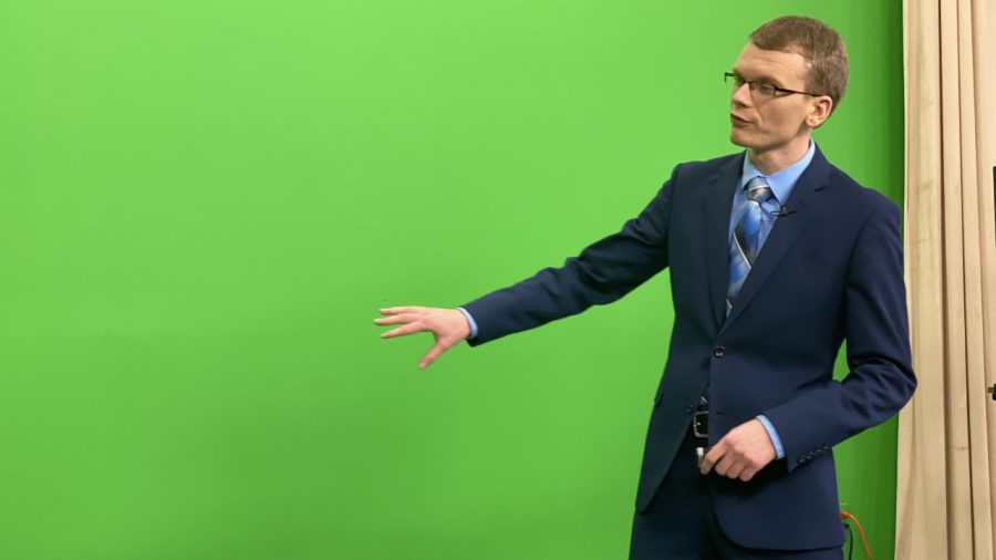 Eastern senior Everett Lau gestures toward a green screen during a broadcast for WEIU Newswatch. Lau has been working for the station since 2017.