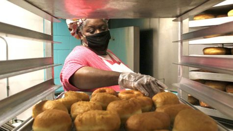 "Marschelle McCoy, the office manager at the biological sciences department and owner of Revival City Doughnuts, makes doughnuts Friday morning at Revival City Doughnuts. She said she loves making people happy with her food. McCoy said that their motto is, ""we make 100 percent awesome doughnuts."""