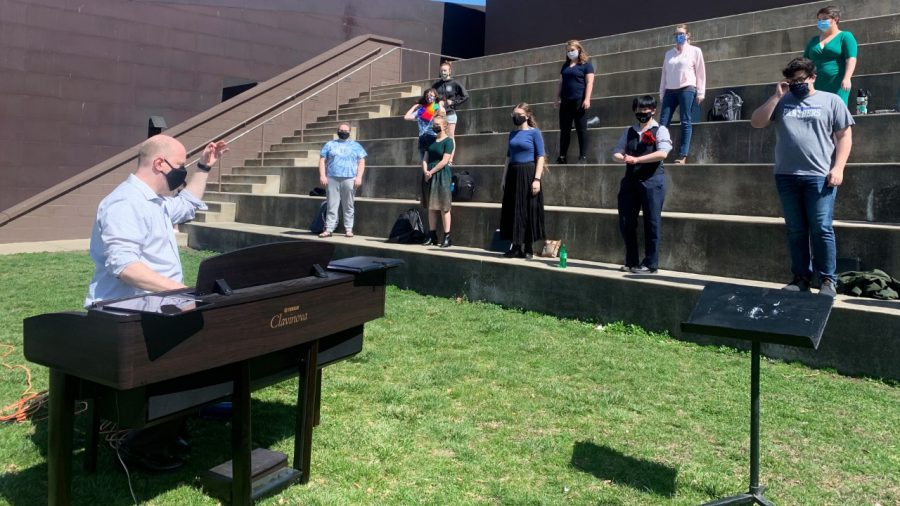 Andrew Martin, choral conductor, conducts concert choir class on the Mellin Steps Wednesday afternoon. Martin explained because singing is an aerosol activity and COVID protocols only a group of ten can sing inside. Now the group can expand because they can sing outside in the warm weather